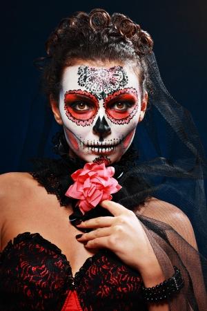 skull character: halloween make up sugar skull beautiful model with perfect hairstyle. Santa Muerte concept.