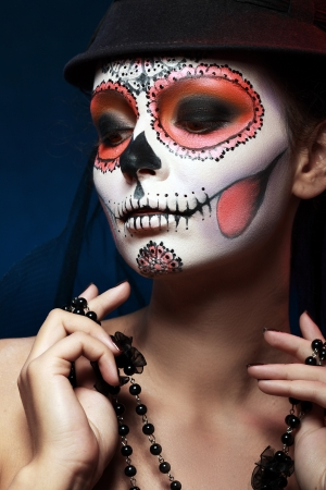mexican folklore: Sugar skull girl in hat, studio shot Stock Photo