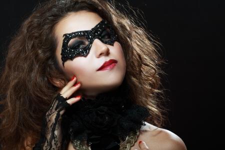Beautiful young woman in black mysterious venetian mask. Fashion photo photo