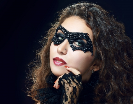 Mask. Girl. Veni ce carnival mask Close-up female portrait.Blue eyes. Black background photo