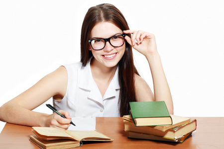 Friendly College student girl in glasses with books at the desk isolated  photo