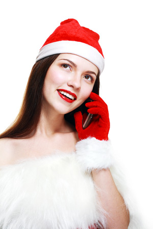 Santa Girl with Cell Phone. Brunette Happy Young Woman with Christmas Hat calling by Mobile.  photo
