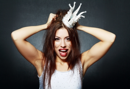 portrait of woman wearing white princess crown with funny and crazy expression on her face photo