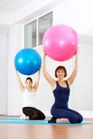 two happy women at the gym with a pilates balls photo