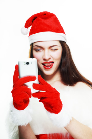 Santa Girl with Cell Phone. Going to take picture by her smartphone. photo