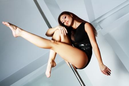 Junge schlanke Pole Dance Frau im Tanzstudio