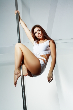 pole dance: Giovane sottile pole dance woman in studio di danza