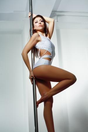 Young slim pole dance woman in dance studio
