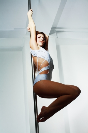 Young slim pole dance woman in dance studio photo