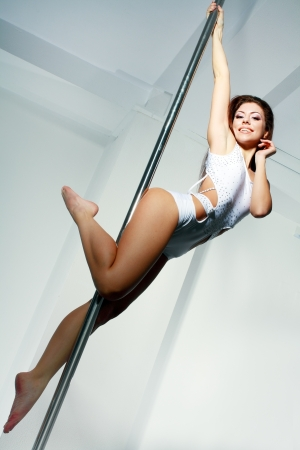 poledance: Young slim pole dance woman in dance studio