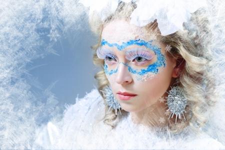 Closeup portrait of beautiful woman with winter style makeup frozen window photo