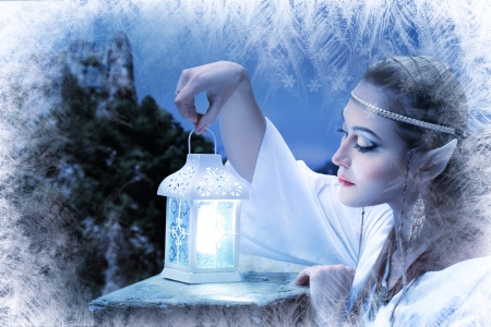 a fairy elf princess with snow ice on winter with lantern in her hand photo