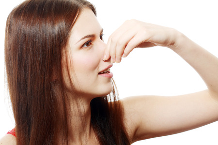 Young Woman Holding her Nose smelling something stinking photo