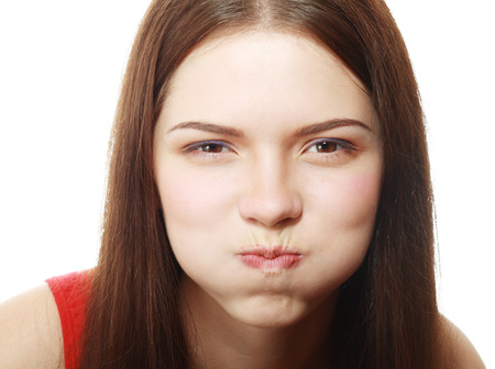 Portrait of disgusted young woman blowing cheeks.White Background,