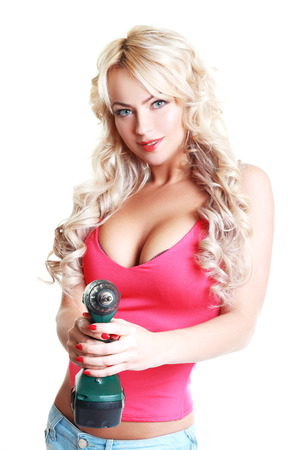 High fashion glamour blondy model in blue jeans, pink top with a screw gun  photo