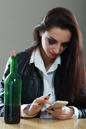 desperation: Young crying woman in depression drunk calling on cell phone