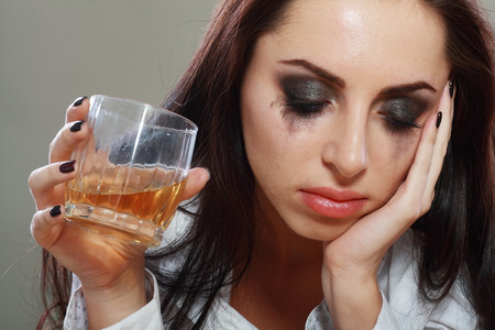 Jonge schreeuwende vrouw in depressie drinkt alcohol