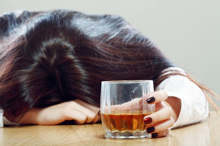 Drunk woman holding an alcoholic drink and sleeping with her head on the table (Focused on the drink Stockfoto