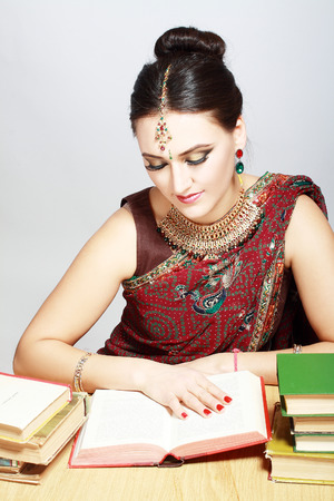 indian style sitting: Beautiful indian woman in traditional national clothes with lot of books sitting at the table and studying