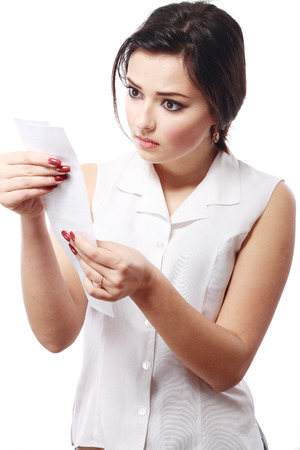 overspending: young woman shocking after checking over the receipt in her hands and spending too much Stock Photo