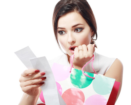 overspending: Shopaholic - Attractive brunette woman looking at her receipt - overspending