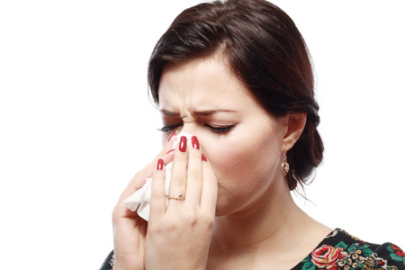 Close-up portrait of a sneezing woman with allergy or cold  版權商用圖片