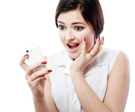 shocked woman staring at her mobile phone in disbelief photo