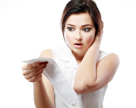 much: young woman shocking after checking over the receipt in her hands and spending too much Stock Photo