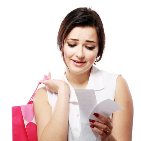 overspending: Shopaholic - Attractive brunette woman looking at her receipt - overspending, Isolated over white background Stock Photo