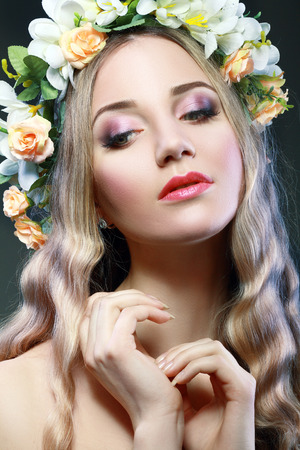 Beautiful Girl With Flowers on Her Head.Beauty Model Woman Face. Perfect Skin. Professional Make-up.Makeup. Fashion Art  photo