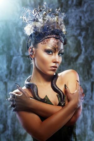 maquillaje de fantasia: Gorgon Medusa en la mazmorra. Mujer joven con el peinado creativo fantas�a y maquillaje Foto de archivo