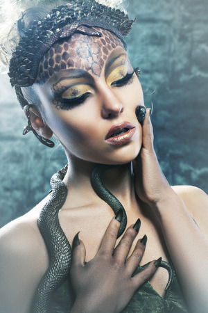 Gorgon medusa in dungeon. Young woman with creative fantasy hairstyle and make up photo