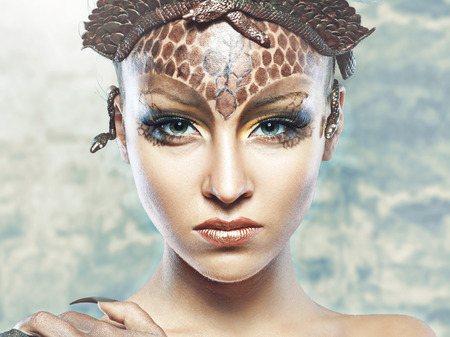 Gorgon medusa in dungeon. Young woman with creative fantasy hairstyle and make up
