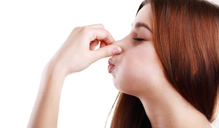 Young Woman Holding her Nose smelling something stinking