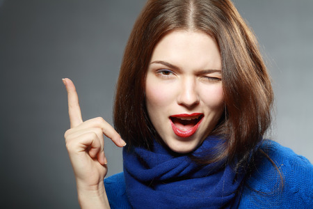 Smiling beautiful woman having an idea close up face pointing up with finger Stock Photo
