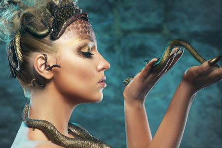 Gorgon medusa. Young woman with creative fantasy hairstyle and make up , holding a snake.