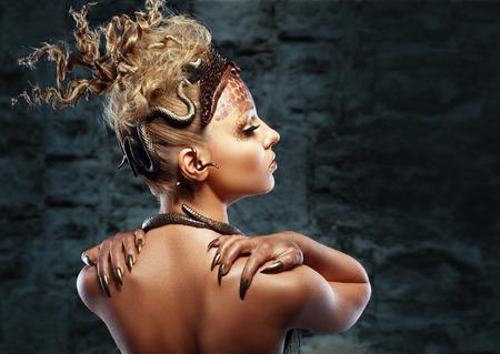 Gorgone Medusa. Giovane donna con creativa fantasia acconciatura e trucco