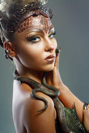 Gorgon medusa. Young woman with creative fantasy hairstyle and make up photo