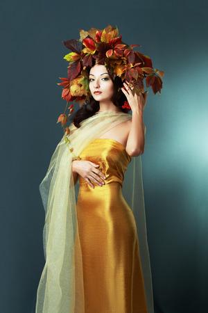 Autumn Woman close up. Beautiful makeup iover orange brown background. viburnum berries photo