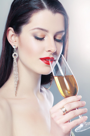 Beautiful young woman in hold a glass of champagne soft colors photo