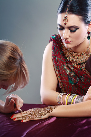 mehandi: A female henna artist applies a henna design to the back of a womans hands.