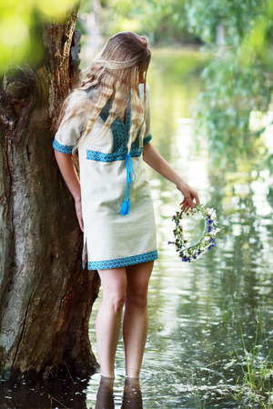Portrait of a young girl on the bank of the river, prepared up for the holiday of Ivan Kupala (John Baptists Day)  photo