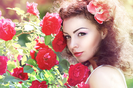 Beautiful brunette fashion model in garden under red roses bower. Fashion toning photo