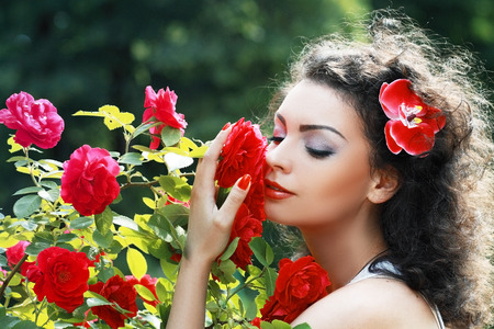 Beautiful brunette fashion model woman in garden smelling red roses photo