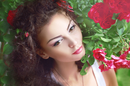 Beautiful brunette fashion model in garden under red roses bower.  photo