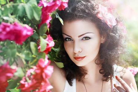 mooie brunette: Mooie brunette fashion model in de tuin onder rode rozen prieel.
