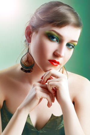 ceremonial make up: Close-up of beautiful female face with green colorful make-up and lips