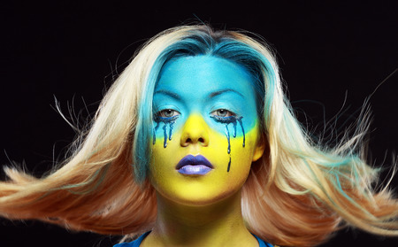 crazy color face art women portrait with yellow and blue as flag of Urkaine. Hair flying over her head photo