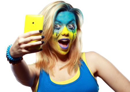 bodypaint: girl with painted face take a self portrait with her smart phone  Stock Photo