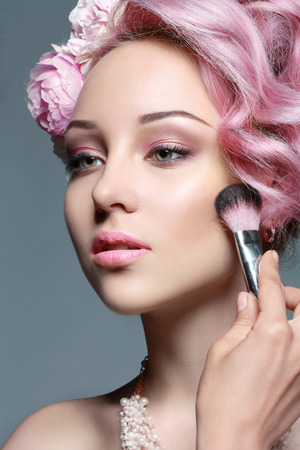 romance image: woman with pink hair and pink lips applying bronzer to cheeks